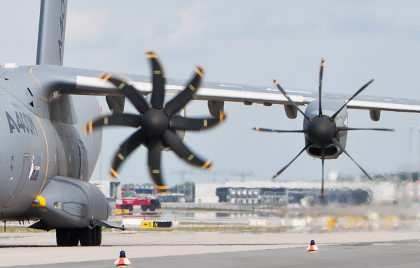 a military aircraft shows one propeller being feathered while the other is still operating