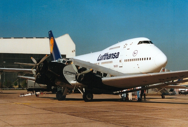 a ju 52 sits in front of a Lufthansa 747