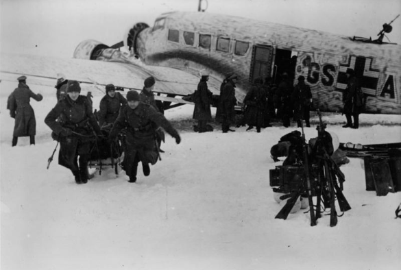 russian soldiers offload men and equipment from a ju 52 in Demyansk Fortress